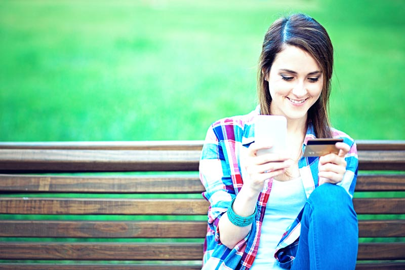 A girl with her iphone sitting a park bench