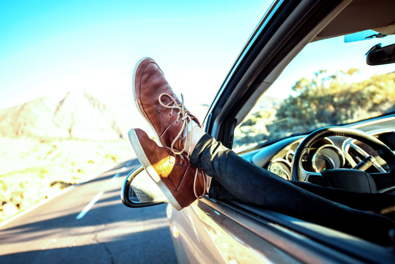 A man relaxing with his feet outside of a car window