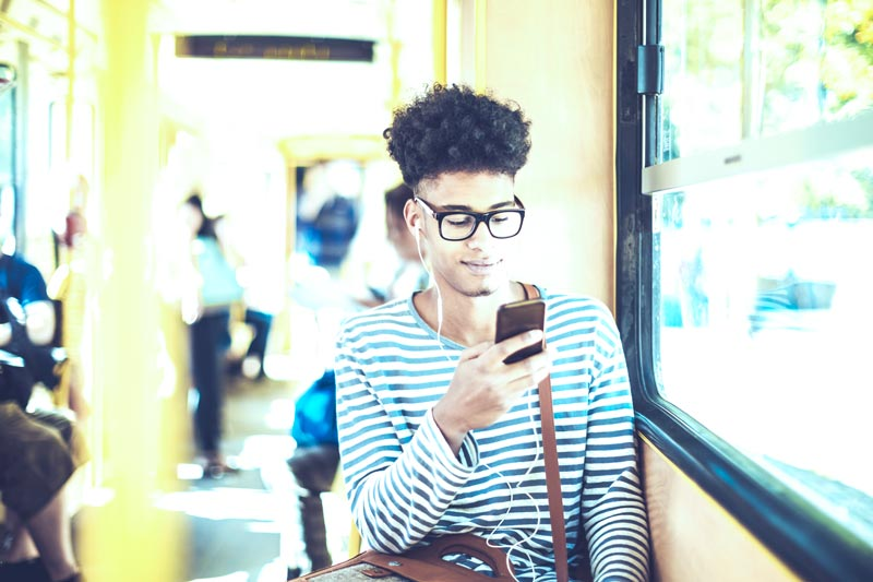 A young man on the bus on his smart phone